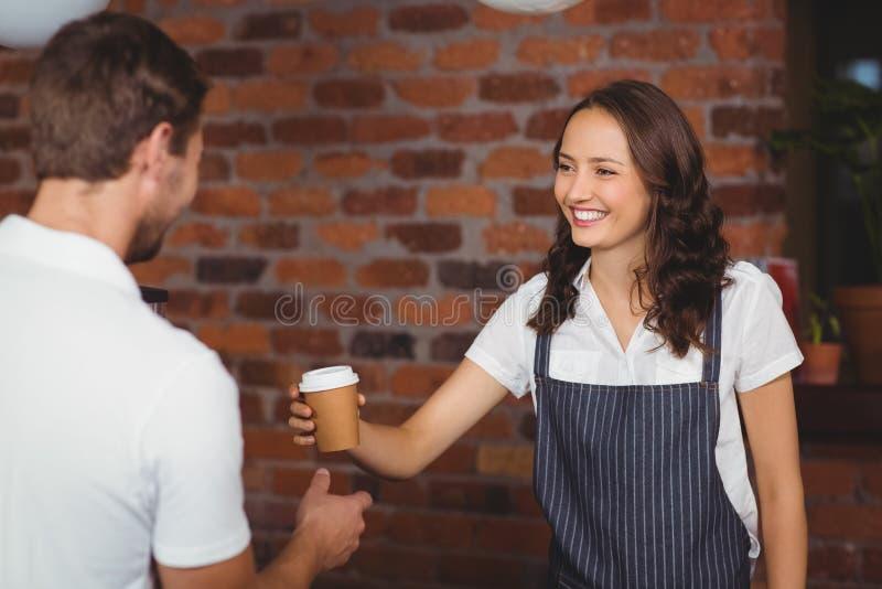 Όμορφο barista χαμόγελου που εξυπηρετεί έναν πελάτη στοκ φωτογραφία