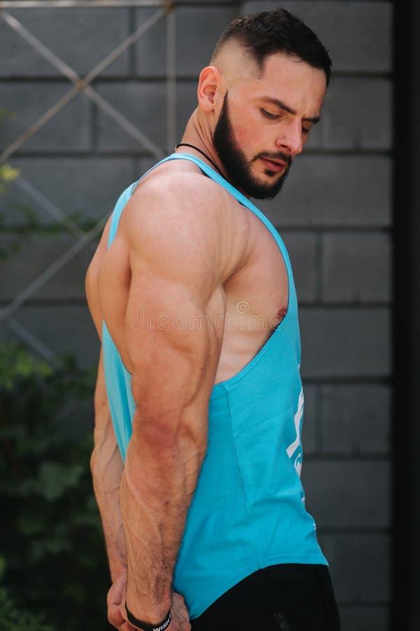 Όμορφο bodybuilder στην μπλε φανέλα που θέτει έξω Άτομα Bearden πρίν εκπαιδεύει στοκ εικόνες με δικαίωμα ελεύθερης χρήσης
