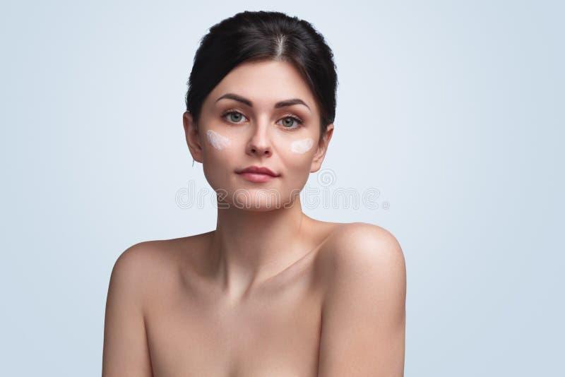 Όμορφο brunette με τις κηλίδες της κρέμας στοκ φωτογραφία με δικαίωμα ελεύθερης χρήσης