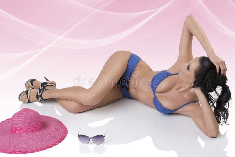 Όμορφο brunette μπλε bikini με το κεφάλι στοκ εικόνα