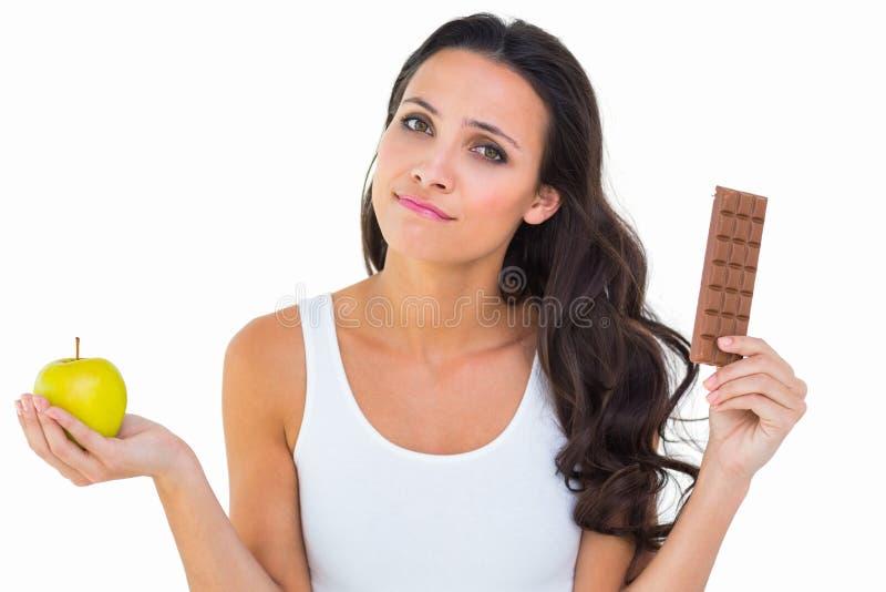 Όμορφο brunette που αποφασίζει μεταξύ του μήλου και της σοκολάτας στοκ εικόνες