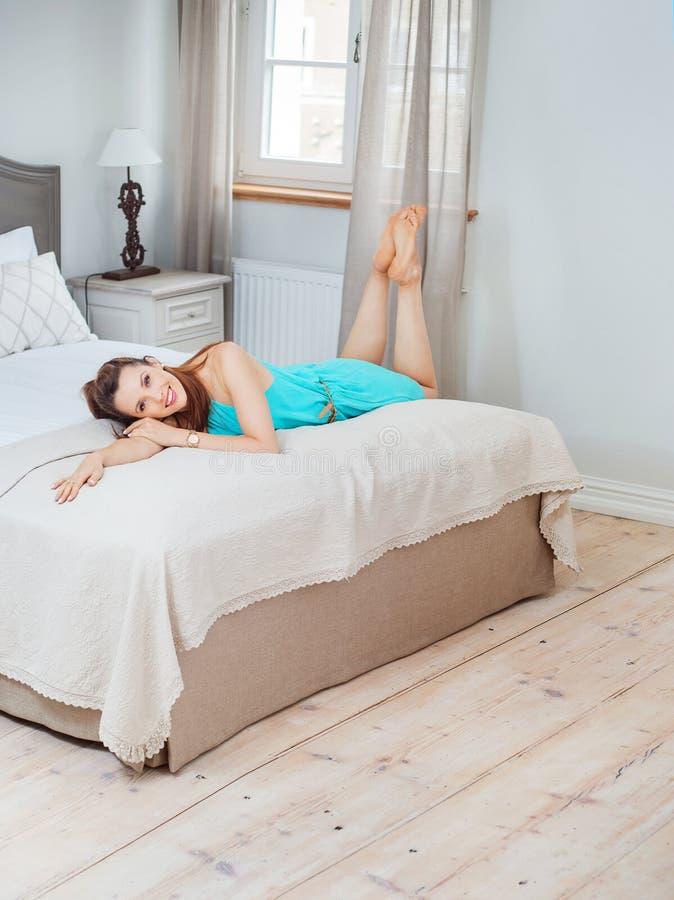 Όμορφο brunette που βρίσκεται στο ευρύ κρεβάτι στοκ φωτογραφία με δικαίωμα ελεύθερης χρήσης