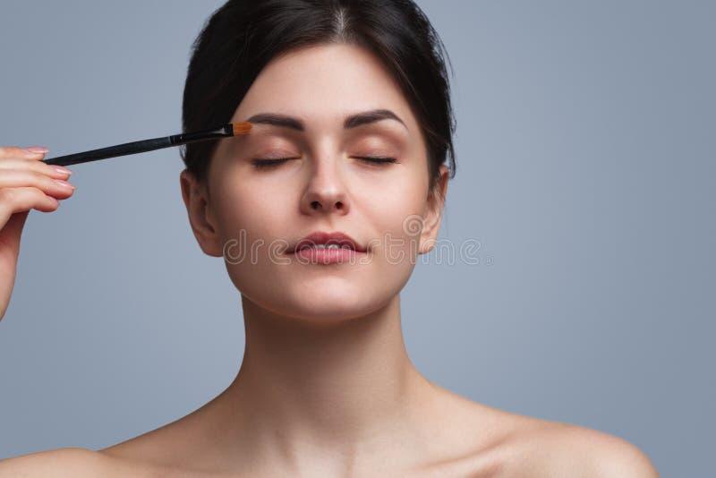 Όμορφο brunette που κάνει makeup στοκ φωτογραφίες