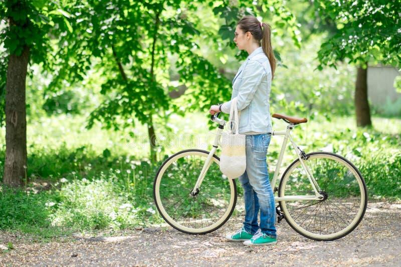 Όμορφο brunette που στέκεται κοντά στο κίτρινο ποδήλατό της στοκ εικόνα με δικαίωμα ελεύθερης χρήσης