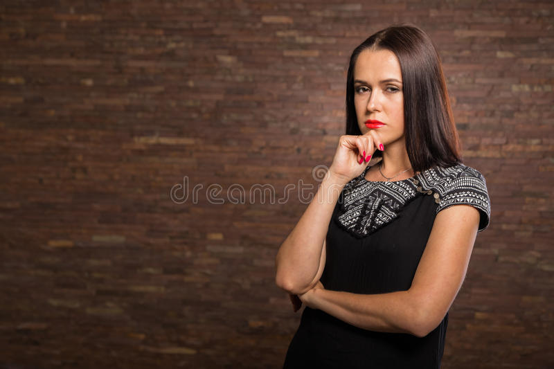 Όμορφο brunette σε ένα μοντέρνο φόρεμα σχεδιαστών σε ένα σκοτεινό υπόβαθρο στοκ εικόνες