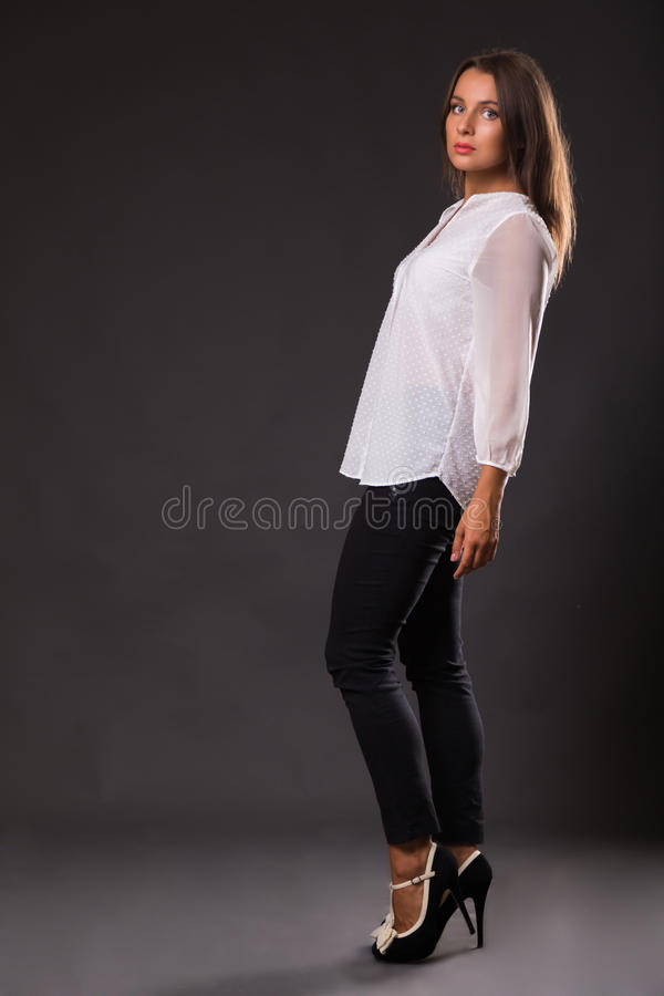 Όμορφο brunette σε μια μοντέρνη μορφή σε ένα σκοτεινό υπόβαθρο στοκ φωτογραφία με δικαίωμα ελεύθερης χρήσης