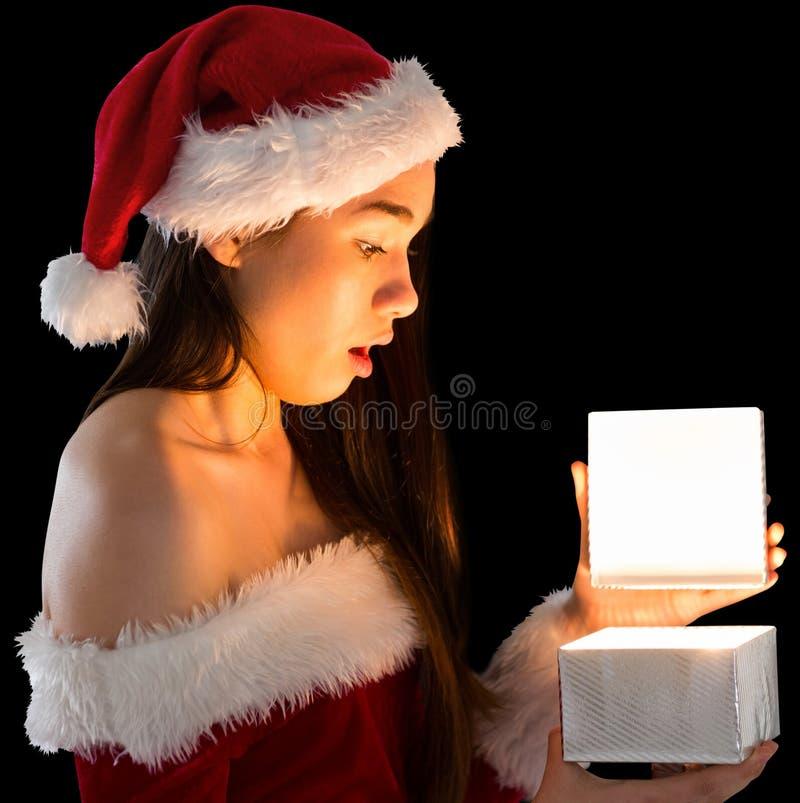 Όμορφο brunette στην εξάρτηση santa που ανοίγει ένα δώρο στοκ εικόνες