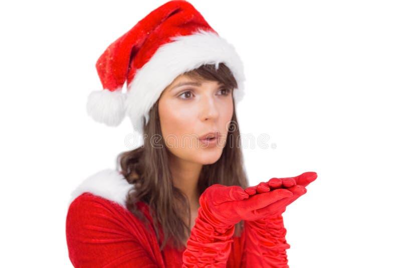 Όμορφο brunette στην εξάρτηση santa που φυσά πέρα από τα χέρια στοκ φωτογραφία με δικαίωμα ελεύθερης χρήσης