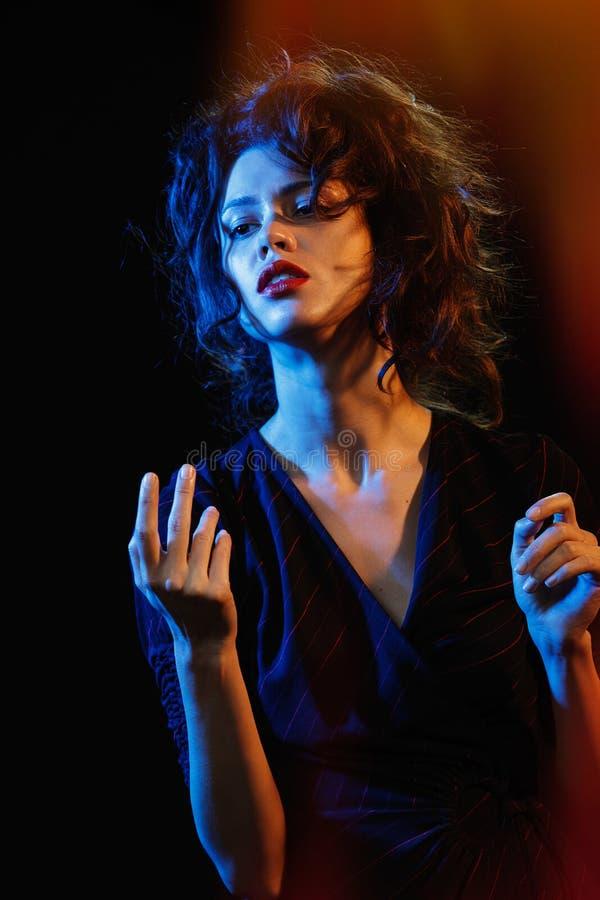 Όμορφο brunette στην πυράκτωση του μπλε και του κόκκινου φωτός στοκ φωτογραφία με δικαίωμα ελεύθερης χρήσης