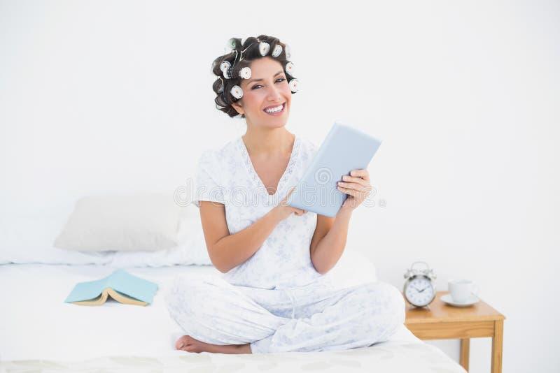Όμορφο brunette στους κυλίνδρους τρίχας που χρησιμοποιούν την ταμπλέτα στο κρεβάτι που χαμογελά στο γ στοκ φωτογραφία