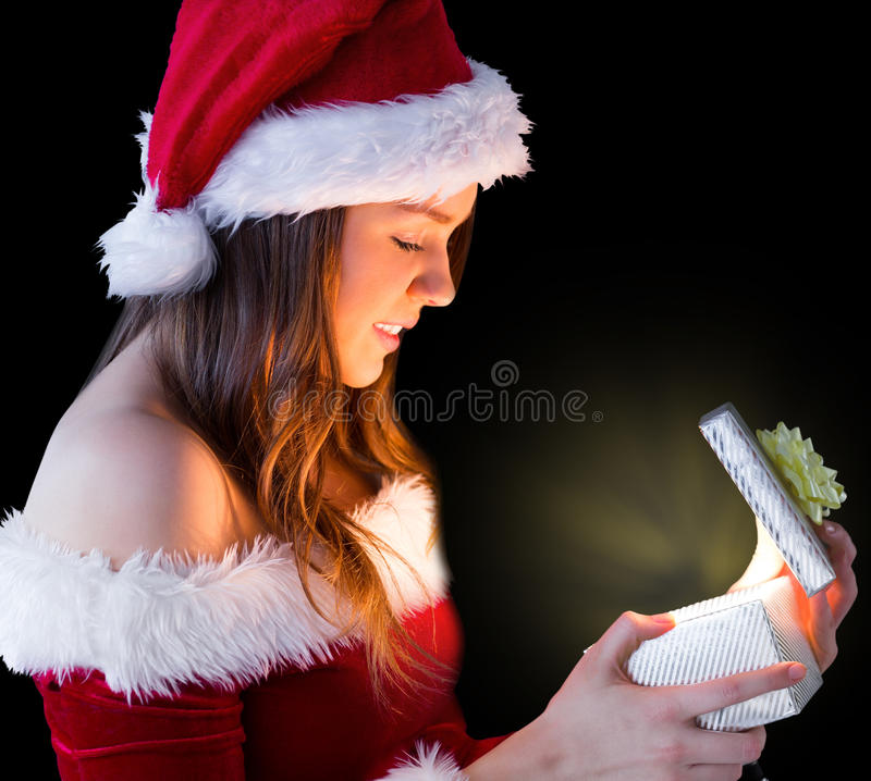 Όμορφο brunette στο δώρο ανοίγματος εξαρτήσεων santa στοκ φωτογραφία με δικαίωμα ελεύθερης χρήσης