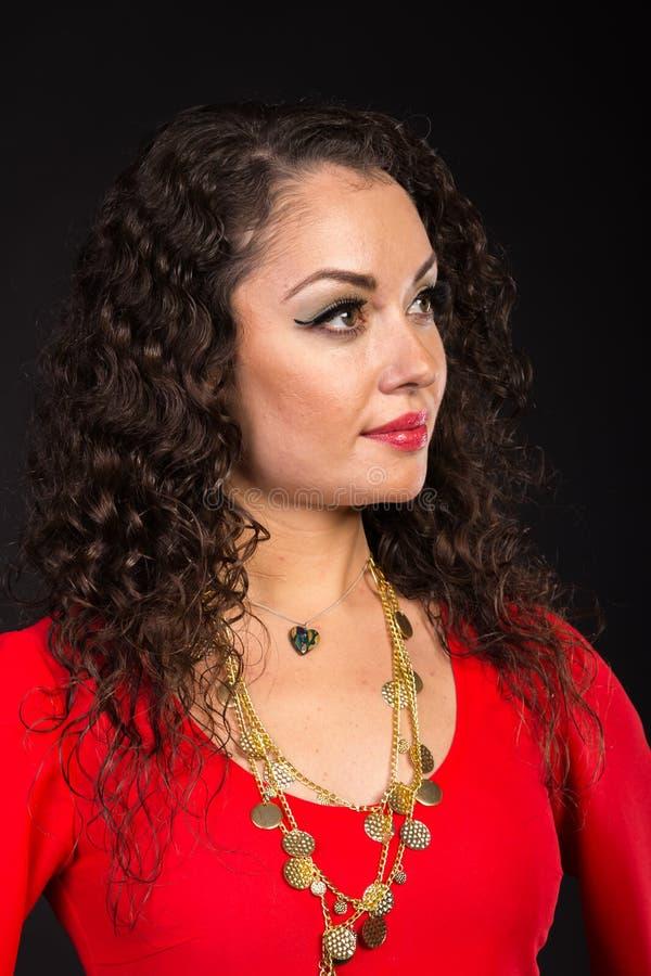 Όμορφο brunette υπό μορφή τσιγγάνου σε ένα σκοτεινό υπόβαθρο στοκ φωτογραφία