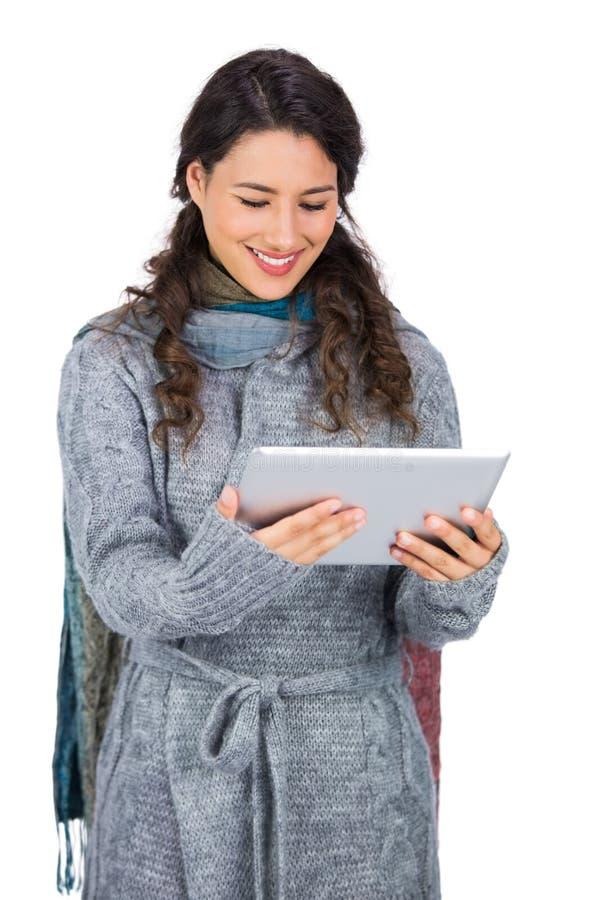 Όμορφο brunette χαμόγελου που φορά τα χειμερινά ενδύματα που κρατούν τον πίνακά της στοκ φωτογραφίες με δικαίωμα ελεύθερης χρήσης
