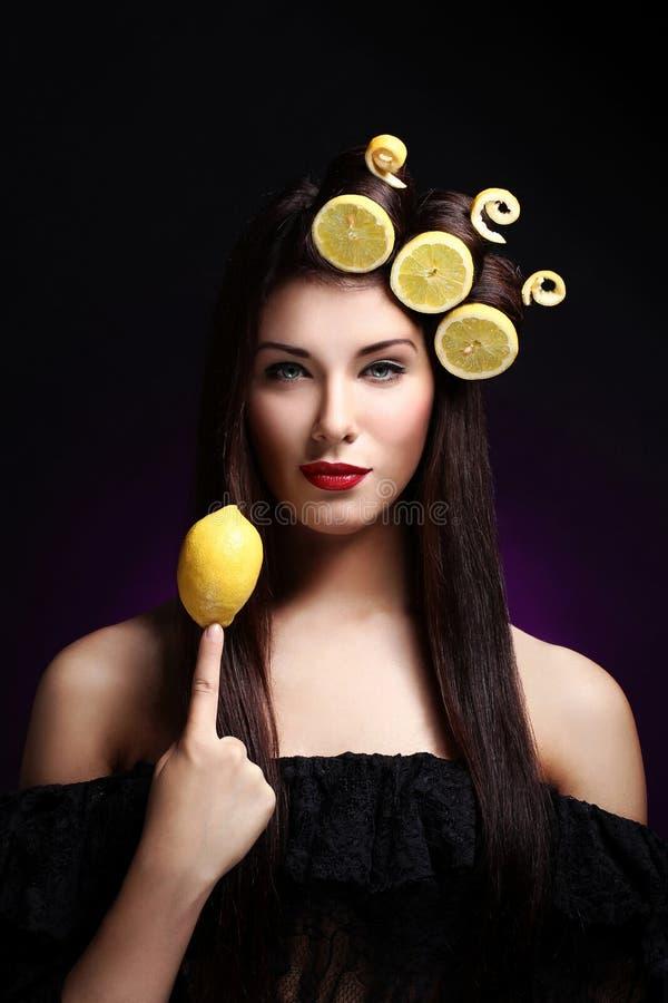 Όμορφο brunnete με τα λεμόνια στο hairstyle της στοκ εικόνα με δικαίωμα ελεύθερης χρήσης