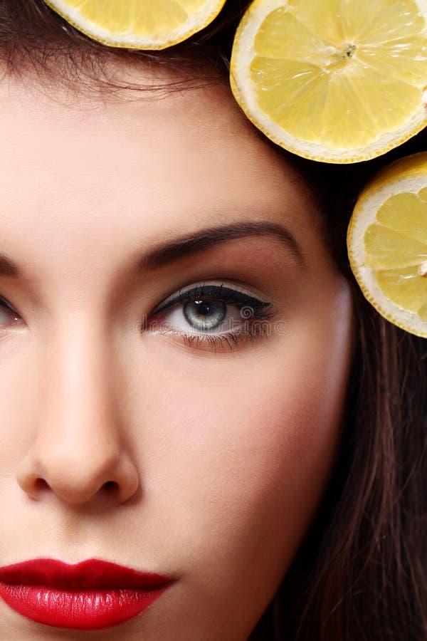Όμορφο brunnete με τα λεμόνια στο hairstyle της στοκ φωτογραφίες
