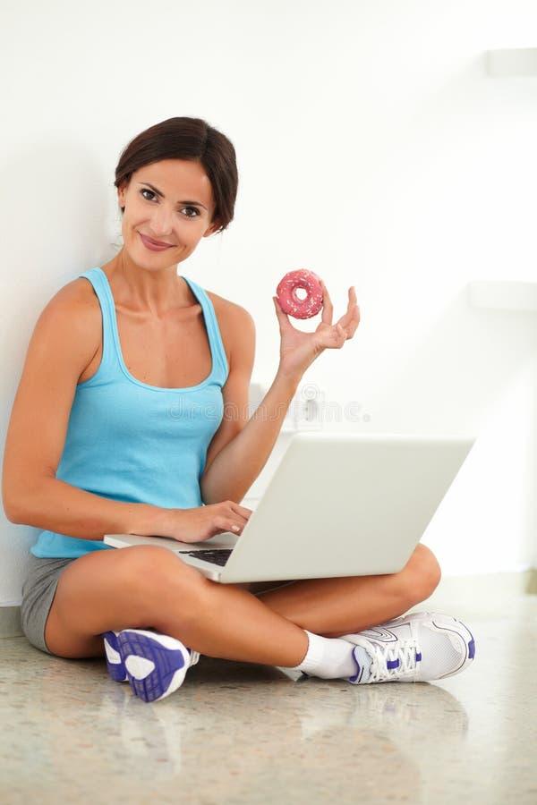 Όμορφο doughnut εκμετάλλευσης γυναικών κάνοντας σερφ τον Ιστό στοκ εικόνα με δικαίωμα ελεύθερης χρήσης
