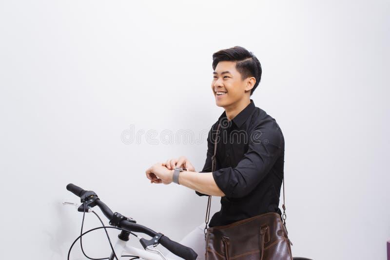Όμορφο hipster που απολαμβάνει έναν γύρο ποδηλάτων και που ελέγχει το χρόνο στο ρολόι του στοκ εικόνα με δικαίωμα ελεύθερης χρήσης