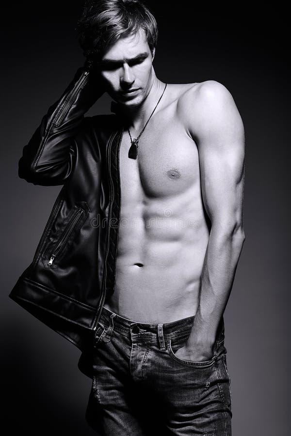 Όμορφο muscled κατάλληλο αρσενικό πρότυπο άτομο στο σακάκι δέρματος στοκ εικόνα