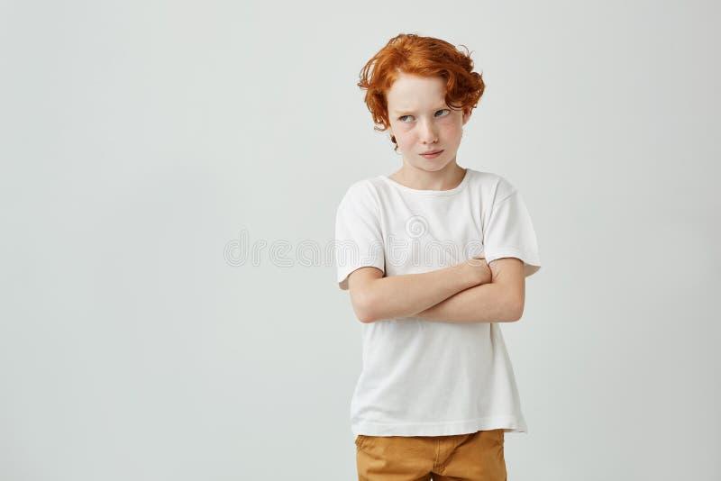Όμορφο redhead αγόρι στην άσπρη μπλούζα που φαίνεται κατά μέρος όντας ανικανοποίητος με το δάσκαλο στο σχολείο που τον επέπληξε σ στοκ φωτογραφία