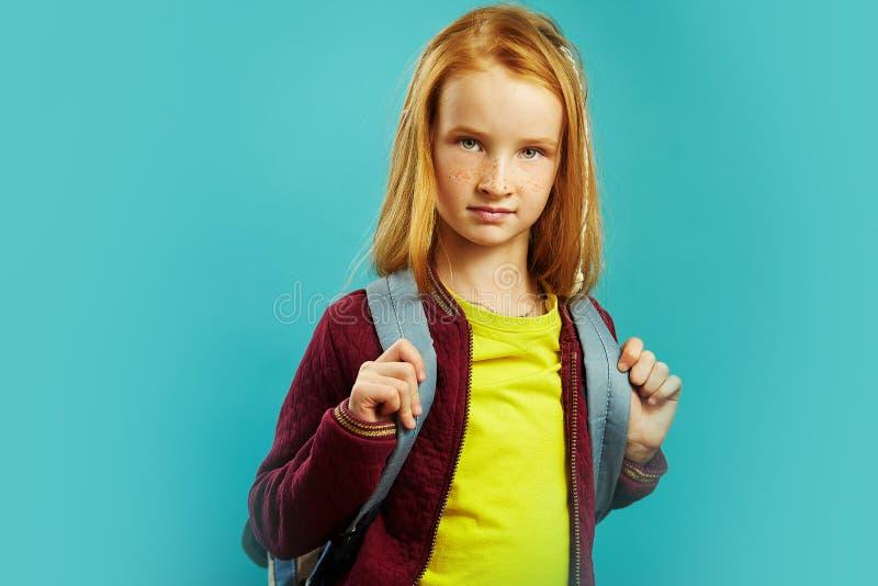 Όμορφο redhead κορίτσι με το σακίδιο πλάτης που απομονώνεται στο μπλε υπόβαθρο πρώτο γκρέιντερ που πηγαίνει στο σχολείο στοκ εικόνα με δικαίωμα ελεύθερης χρήσης