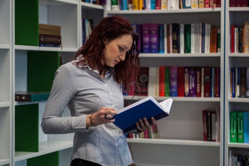 Όμορφο redhead κορίτσι που μελετά στη βιβλιοθήκη Ανάγνωση ενός βιβλίου W στοκ εικόνες με δικαίωμα ελεύθερης χρήσης