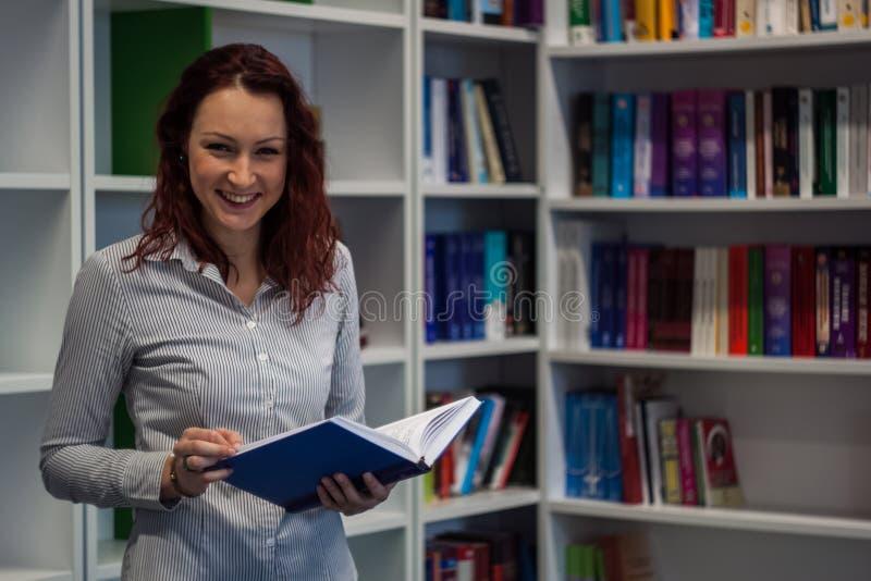 Όμορφο redhead κορίτσι που μελετά στη βιβλιοθήκη Ανάγνωση ενός βιβλίου W στοκ φωτογραφία