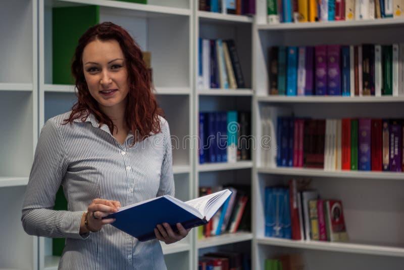 Όμορφο redhead κορίτσι που μελετά στη βιβλιοθήκη Ανάγνωση ενός βιβλίου W στοκ φωτογραφία με δικαίωμα ελεύθερης χρήσης
