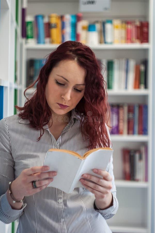 Όμορφο redhead κορίτσι σπουδαστών ευτυχές ευγενικά διαβάζοντας ένα βιβλίο ι στοκ φωτογραφία με δικαίωμα ελεύθερης χρήσης