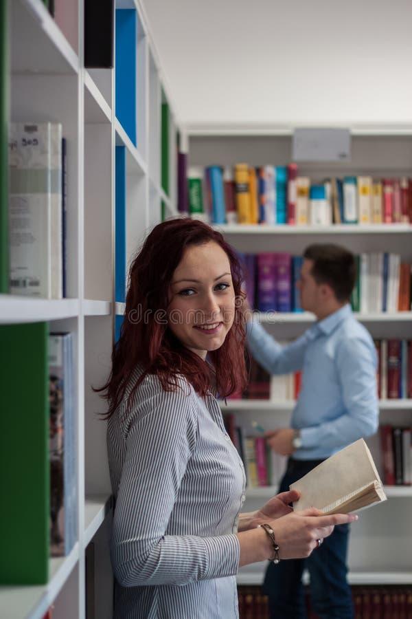 Όμορφο redhead σπουδαστών κοριτσιών βιβλίο εκμετάλλευσης χαράς ευτυχές στο κίνημα απελευθέρωσης στοκ εικόνα με δικαίωμα ελεύθερης χρήσης