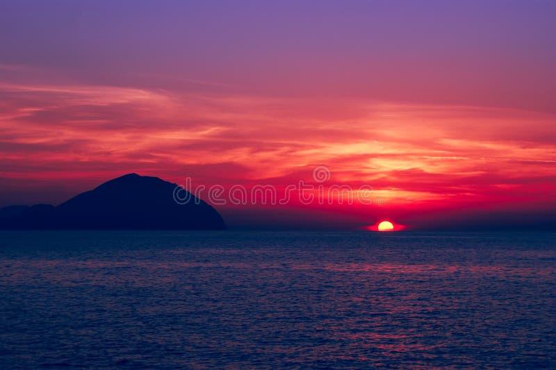 όμορφο seascape ηλιοβασίλεμα Διαποτισμένα χρώματα, σκιαγραφία ενός δύσκολου νησιού στη θάλασσα στοκ εικόνα με δικαίωμα ελεύθερης χρήσης