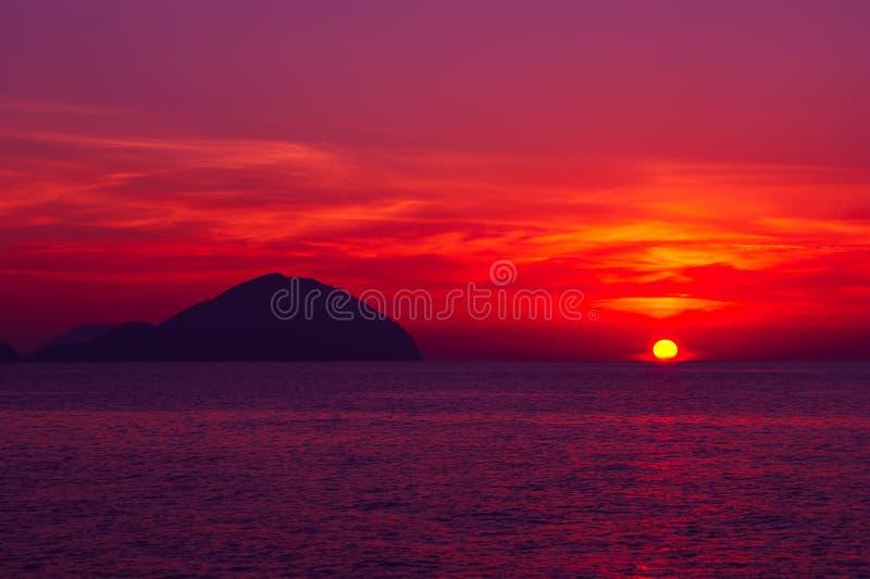 όμορφο seascape ηλιοβασίλεμα Διαποτισμένα χρώματα, σκιαγραφία ενός δύσκολου νησιού στη θάλασσα στοκ εικόνα