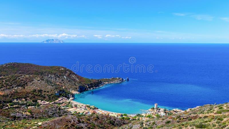 Όμορφο seascape με την παραλία και τη παραλιακή πόλη με έναν φάρο στον κόλπο Giglio Island Isola del Giglio, Τοσκάνη, Ιταλία στοκ φωτογραφίες