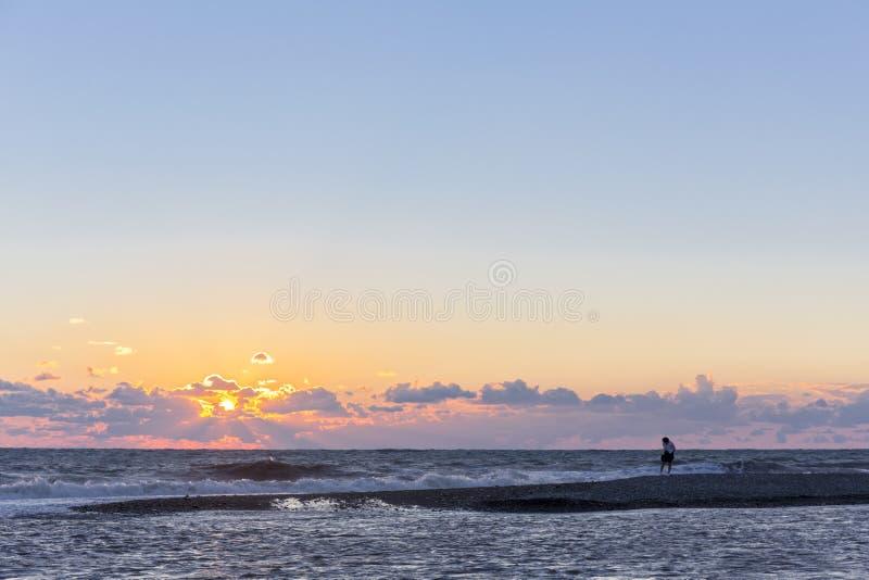 Όμορφο seascape με το ηλιοβασίλεμα και τη γυναίκα στοκ εικόνες