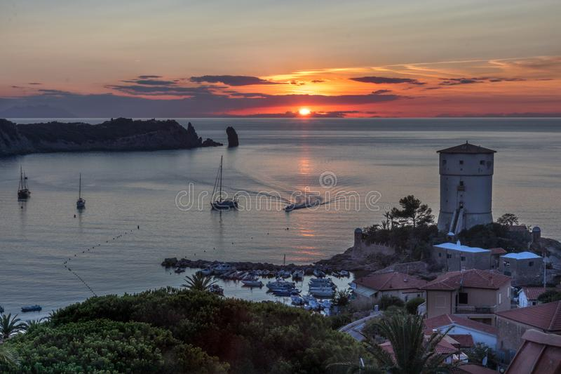 Όμορφο seascape στο ηλιοβασίλεμα με έναν φάρο και τις βάρκες Giglio Island Isola del Giglio, Τοσκάνη, Ιταλία στοκ εικόνα με δικαίωμα ελεύθερης χρήσης