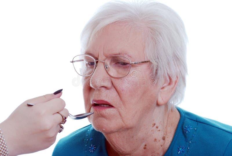 όντας ηλικιωμένη δεδομένη γυναίκα ιατρικής στοκ εικόνα