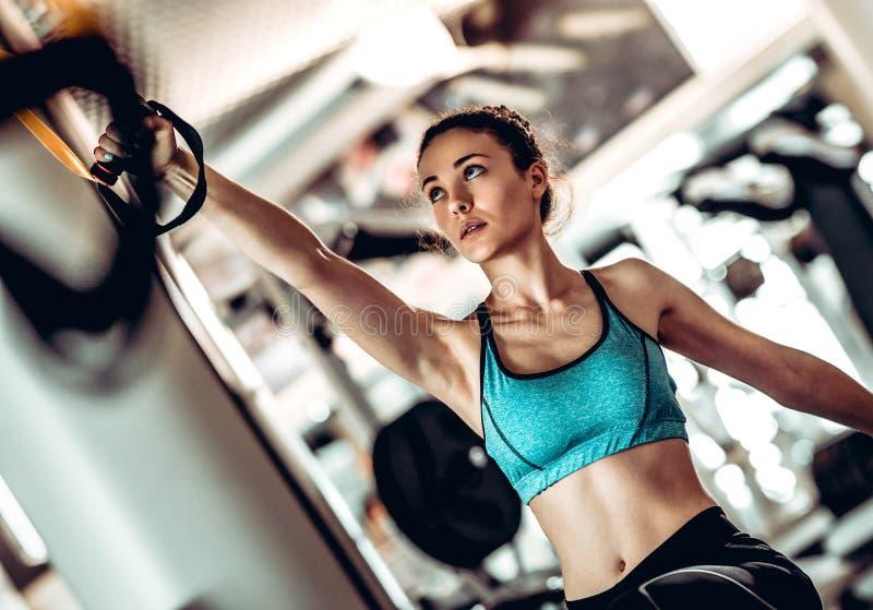 Όπλα κατάρτισης γυναικών με τα λουριά ικανότητας trx στη γυμναστική στοκ εικόνα με δικαίωμα ελεύθερης χρήσης