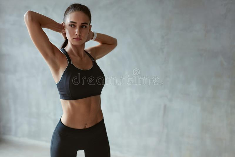 Όπλα τεντώματος γυναικών ικανότητας στα μοντέρνα μαύρα αθλητικά ενδύματα στοκ εικόνες με δικαίωμα ελεύθερης χρήσης