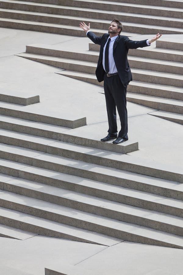 Όπλα Outstretched επιχειρησιακών ατόμων επιχειρηματιών στα βήματα στοκ εικόνες