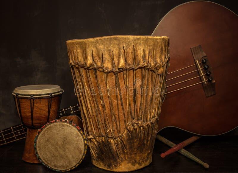Όργανα μουσικής - τύμπανα Djembe και ακουστική βαθιά κιθάρα στοκ φωτογραφίες