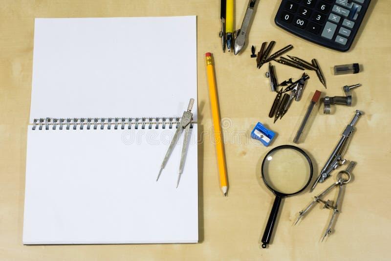 Όργανα σχεδίων και ένα σημειωματάριο στον πίνακα εργασίας Accessorie στοκ εικόνες