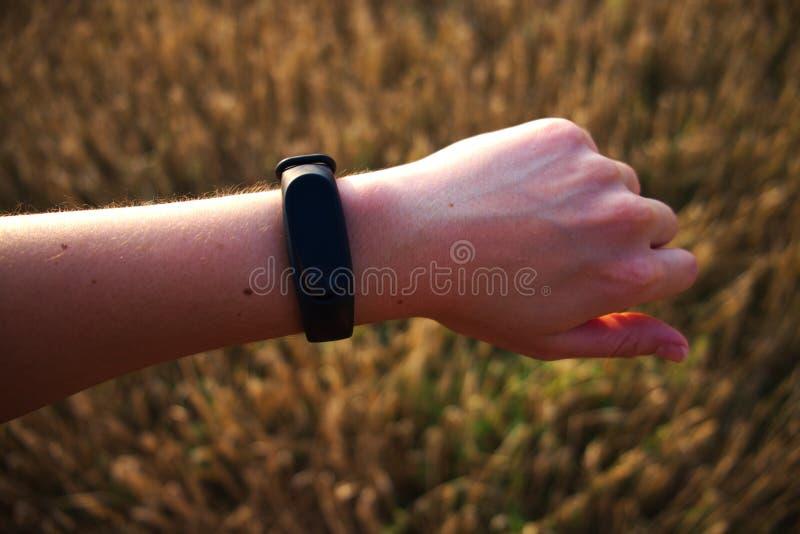 Όργανο ελέγχου δραστηριότητας wristband στον καρπό γυναικών με το χρυσό υπόβαθρο κατά τη διάρκεια του s στοκ φωτογραφία