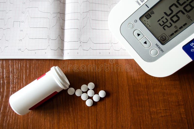 Όργανο ελέγχου πίεσης του αίματος, έντυπο καρδιογραφημάτων, και άσπρα χάπια που ανατρέπουν από ένα μπουκάλι στοκ εικόνα με δικαίωμα ελεύθερης χρήσης