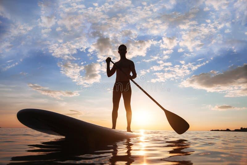 Όρθιο κουπί, κουπί που στέκεται, σκιαγραφία του ατόμου στην παραλία στοκ φωτογραφίες