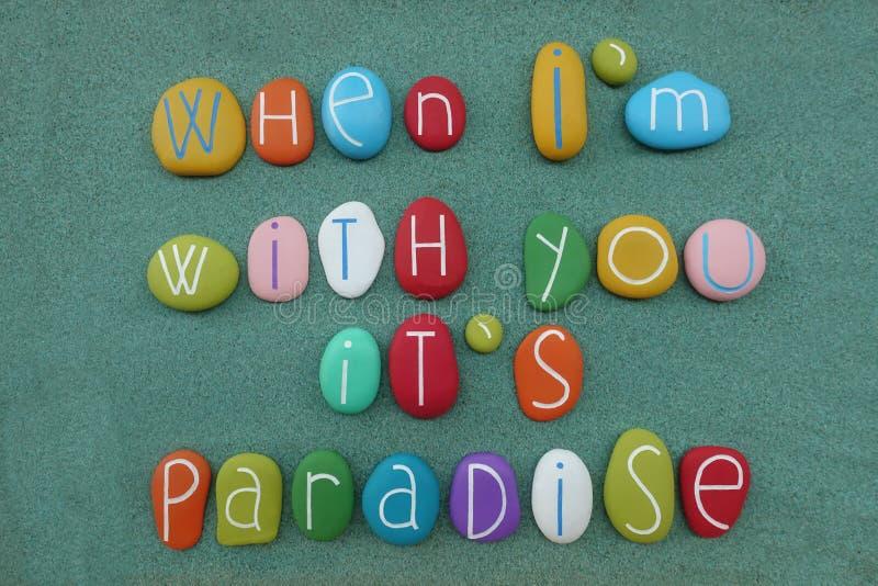 Όταν είμαι με σας, είναι παράδεισος, μήνυμα αγάπης που συντίθεται με τις πολυ χρωματισμένες πέτρες θάλασσας πέρα από την πράσινη  στοκ εικόνα