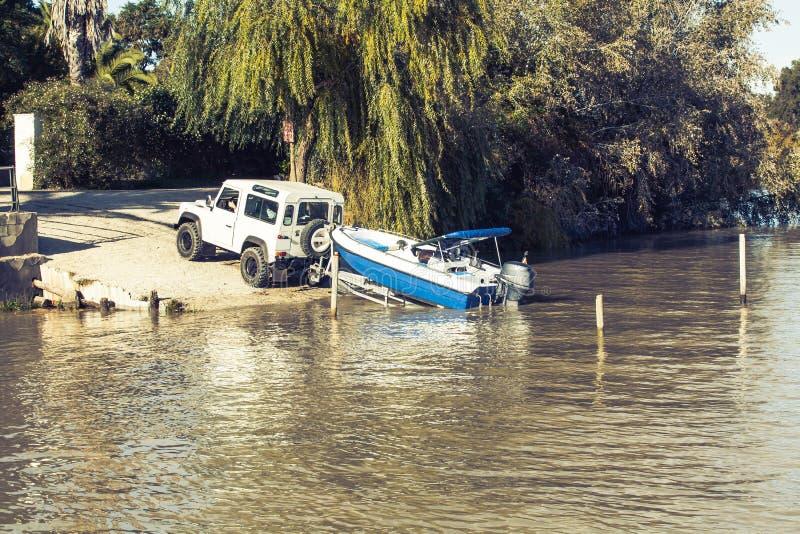 Όλο το όχημα εκτάσεων που ρυμουλκεί ένα ρυμουλκό με μια βάρκα στην κορυφή στον ποταμό στοκ εικόνα