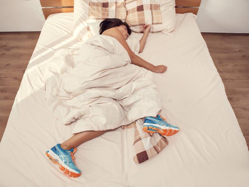 Ύπνοι γυναικών στο κρεβάτι με τα τρέχοντας παπούτσια της επάνω στοκ εικόνες με δικαίωμα ελεύθερης χρήσης