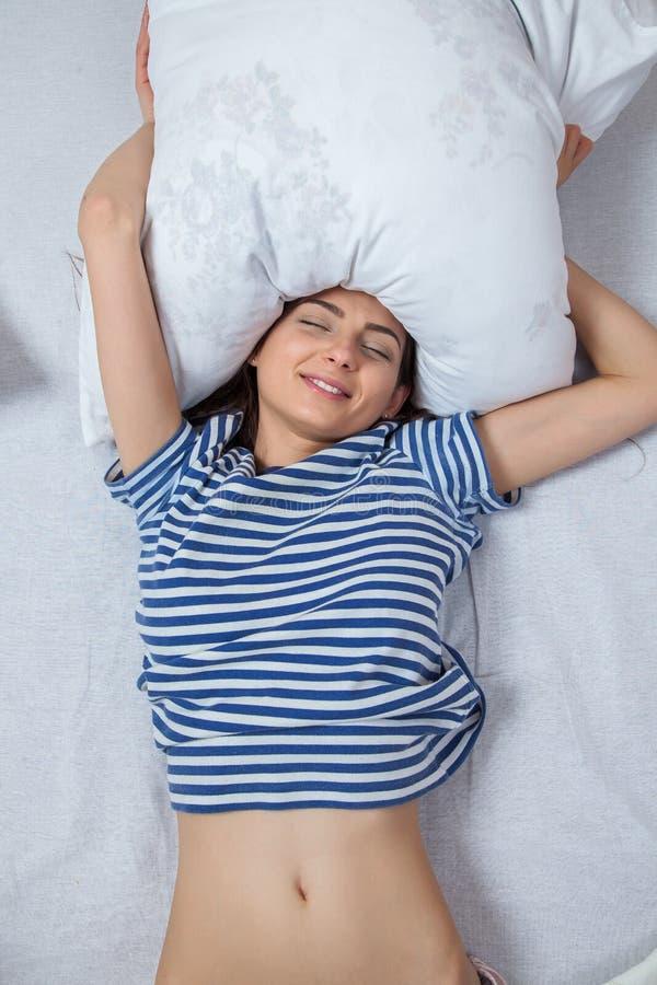 Ύπνοι κοριτσιών σε ένα άσπρο κρεβάτι στο σπίτι Νέος ύπνος γυναικών στα πιτζάματα στο άσπρο λινό στο κρεβάτι στο σπίτι, τοπ άποψη στοκ εικόνα