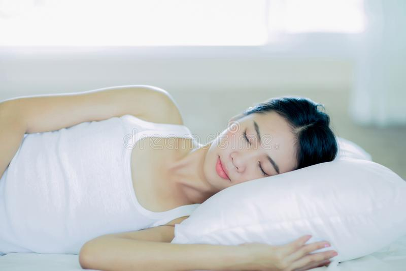 Ύπνοι κοριτσιών Asain στο άσπρο κρεβάτι στοκ εικόνα