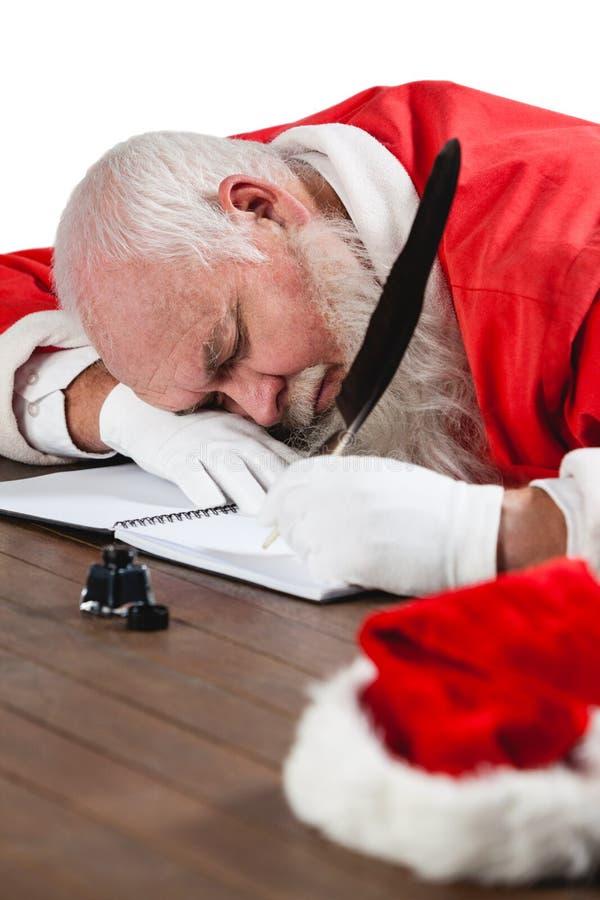 Ύπνος Άγιου Βασίλη στο γραφείο γράφοντας μια επιστολή με ένα καλάμι στοκ φωτογραφία με δικαίωμα ελεύθερης χρήσης