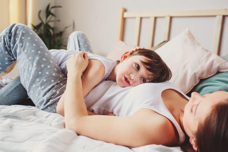 Ύπνος γιων μητέρων και παιδιών μαζί στο κρεβάτι, που ξυπνά το πρωί στοκ εικόνα
